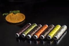 Sete rolos em cores do outono no fundo preto com uma abóbora pequena de feltro, fim acima imagem de stock royalty free