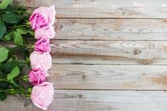 Sete rosas no fundo de madeira Fotografia de Stock