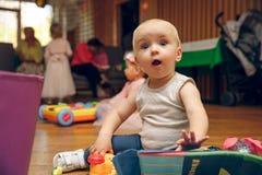 Seten av krypning behandla som ett barn eller litet barn med toys förvånade barnlekar med leksaker Royaltyfri Foto
