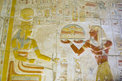 Seti offering food to the goddess Hathor. The Ancient egyptian Pharaoah Seti offering a tray of food to the goddess Hathor, wearing her crown of cow horns. The Royalty Free Stock Photos