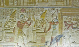 Seti with Osiris Bas Relief. Ancient Egyptian carving of Pharaoh Seti I holding his flail before the god of the underworld Osiris with Horus behind him.  Abydos Royalty Free Stock Photos