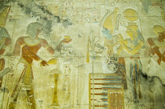 Seti with Osiris and Isis bas relief. Ancient Egyptian bas relief carving showing the Pharaoh Seti I making an offering of incense to the god of the underworld stock images