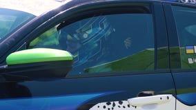 Setkarz w hełmie siedzi w samochodzie i spojrzeniach przy kamerą zdjęcie wideo