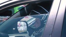 Setkarz w hełmie siedzi w spojrzeniach i samochodzie wokoło, zwolnione tempo zbiory wideo
