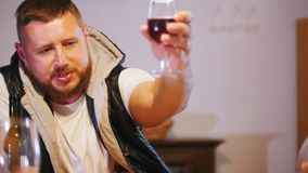 Setout. A man pours a glass of wine and offers to clink. Moves camera stock video