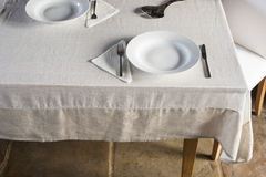 Sets of Dinnerware Arranged on White Linen-Covered Table Stock Photo