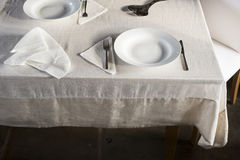 Sets of Dinnerware and Crumpled Napkin on White Linen-Covered Ta Royalty Free Stock Images