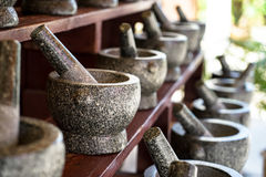 Sets of mortar and pestle in grey and black color granite stone arranging on wooden shelf for sale in local market Stock Photo