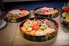 Sets of sushi nigiri, rolls and sashimi served in traditional Japan black Sushioke round plate stock photography