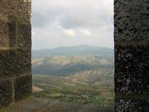 Sett av fönstret av en fasthet av kullarna av Tuscanen i dalen av Orcia Radicofani italy royaltyfri foto