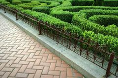 Sett, wrought-iron fence and ornamental hedge Royalty Free Stock Images
