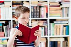 Sette anni del ragazzo che legge un libro in biblioteca Fotografie Stock