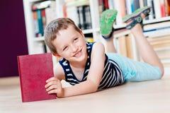 Sette anni del ragazzo che legge un libro in biblioteca Immagini Stock Libere da Diritti