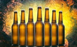 Sette bottiglie di birra di vetro isolate su vecchio fondo nero giallo Fotografia Stock