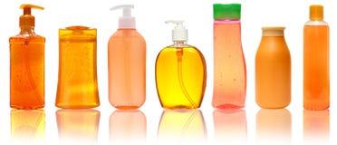 Sette bottiglie di plastica arancio con sciampo, sapone liquido, gel della doccia Isolato su priorità bassa bianca con la rifless Fotografie Stock Libere da Diritti