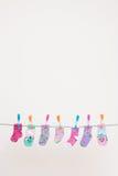 Sette calzini dei bambini sulla linea di lavaggio fotografie stock