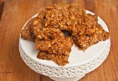 Sette di recente arachidi al forno, barre della noce di cocco sul piatto bianco dell'esposizione fotografia stock