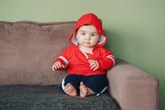 Sette mesi di bambino che si siede sullo strato a casa che guarda in camera Fotografia Stock Libera da Diritti