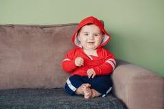Sette mesi di bambino che si siede sullo strato a casa che guarda in camera Immagine Stock