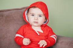 Sette mesi di bambino che si siede sullo strato a casa che guarda in camera Immagine Stock Libera da Diritti