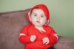 Sette mesi di bambino che si siede sullo strato a casa che guarda in camera Fotografie Stock Libere da Diritti