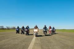 Sette motociclisti stanno guidando lungo la strada del campo fotografia stock libera da diritti