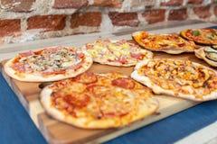 Sette pizze su un bordo di legno, fresco dal forno con il fuoco sulla pizza di carbonara immagini stock libere da diritti