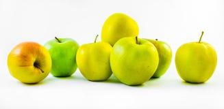 Sette verdi e mele gialle su un fondo bianco Immagine Stock