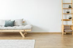 Settee in beige living room. Copy space of white wall and carpet on the floor in beige living room with decoration on wooden shelves near a settee with pillows royalty free stock photos