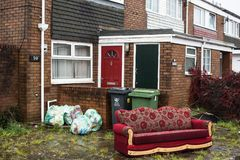 Settee and refuse outside a house. A settee in front of a house, bins and refuse bags ready for recycling Stock Photos