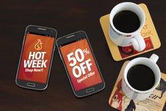 Settimana calda 50% fuori dagli sconti Annunciando, offerta speciale Due telefoni cellulari e due tazze di caffè sopra la tavola  Fotografia Stock Libera da Diritti