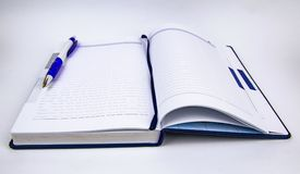 Settimanale aperto con la penna su fondo bianco fotografia stock