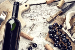 Setting with bottle of red wine, grape and corks Royalty Free Stock Photos