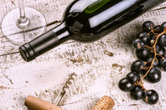 Setting with bottle of red wine, grape and corks Royalty Free Stock Images