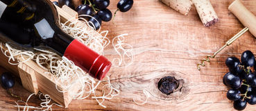 Setting with bottle of red wine, grape and corks. Royalty Free Stock Photography
