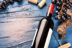 Setting with bottle of red wine, grape and corks. Wine list conc. Ept over blue background Royalty Free Stock Image