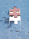 Setting the brown last piece of puzzle Stock Photos