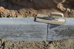Setting a curbstone. Setting a concrete cornerstone in fresh cement Royalty Free Stock Photo