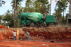 Setting footers Concrete truck. Worker setting footer on new home construction site with concrete truck Stock Images