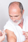 Setting an injection on the arm of an elderly man. Setting an injection in the biceps of a man Stock Photo
