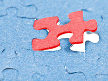 Setting the last red piece of puzzle Stock Photos