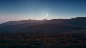 Setting moon over the mountains. Picturesque mountain scene with crescent moon and stars on the twilight sky stock footage