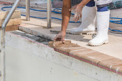 Setting new brick coping pool remodel. Cement work and repairs to top of pool beam prep for pool remodel new brick coping Stock Photo