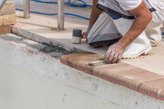 Setting new brick coping pool remodel. Craftsman setting new brick coping Stock Image