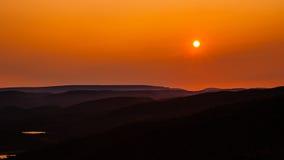 Setting orange sun over hills receding into hazy distance Stock Photography