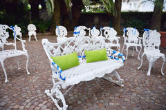 Setting for outdoors wedding ceremony with decorated chairs and bench for bride and groom Stock Photo