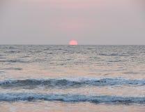 Setting Red Sun at Horizon over Sea at Payyambalam Beach, Kannur, Kerala, India Stock Image