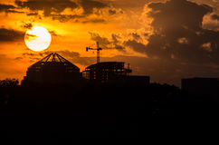 Setting sun above scaffolding and buildings. Stock Photos