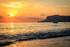 The setting sun in Alanya. Coast and boat drifting on the water Stock Images