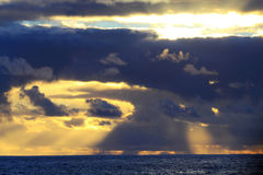 Setting sun behind the clouds Stock Photo